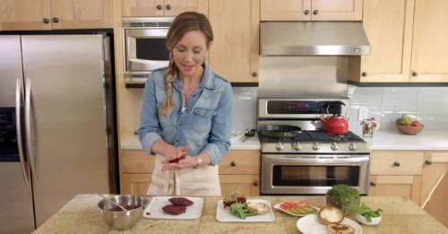Woman in a kitchen making hamburger patties.
