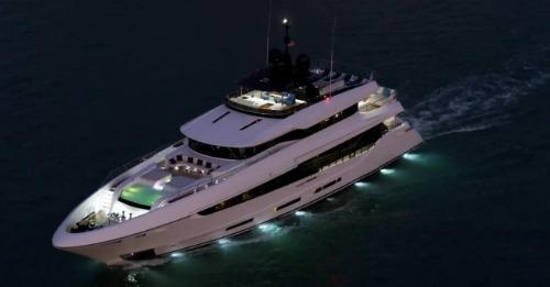 Yacht at sea with lights shining in water at nightfall.