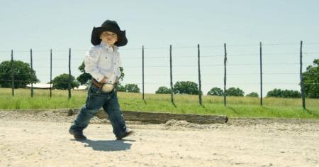 Little boy walking wearing a black cowboy hat and big belt buckle.